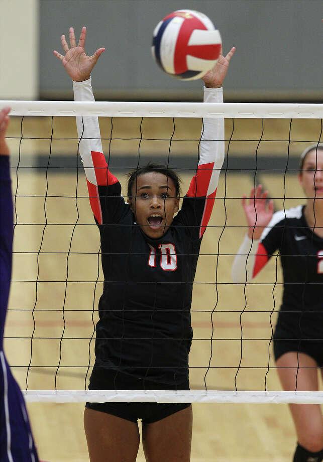 Churchill's Dariann Gilford (10) reaches for a block against Warren in volleyball at Littleton Gym on Tuesday, Aug. 13, 2013. Photo: Kin Man Hui, San Antonio Express-News / ©2013 San Antonio Express-News