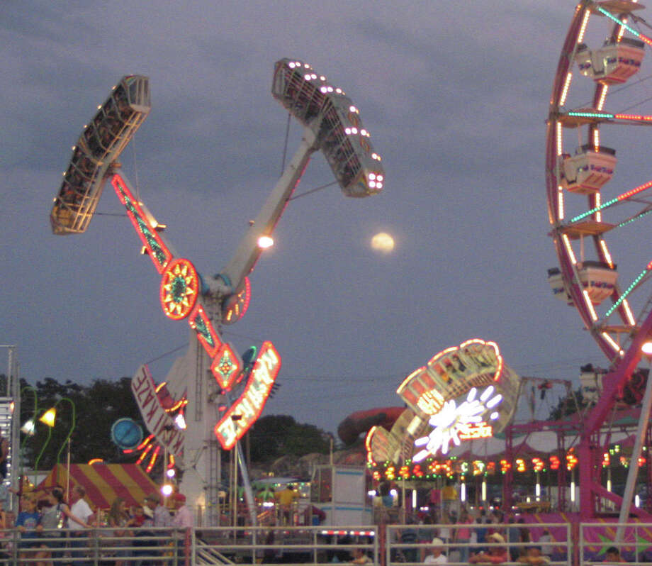 A full moon shines over the glowing midway at the Washington County Fair.