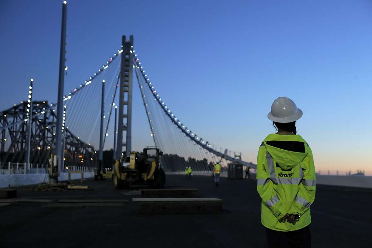 Chelsea Wurms with MTC looks at the tower of the new section of the San Francisco-Oakland Bay Bridge after it was lighted on Tuesday, August 11, 2013, as members of the MTC, Caltrans and the press took a walking tour of the new structure in San Francisco, Calif.