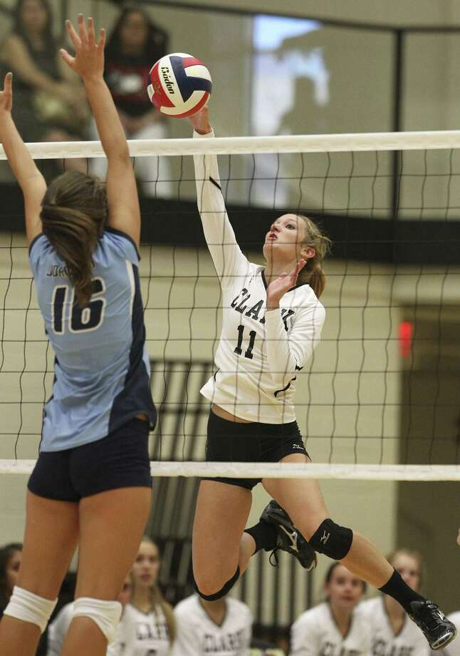 Clark's Katie Mattson takes a swing as Johnson's Lauren Bault defends at Littleton Gym. Clark escaped with a five-set victory in a back-and-forth match that lasted two hours. Photo: Kin Man Hui / San Antonio Express-News