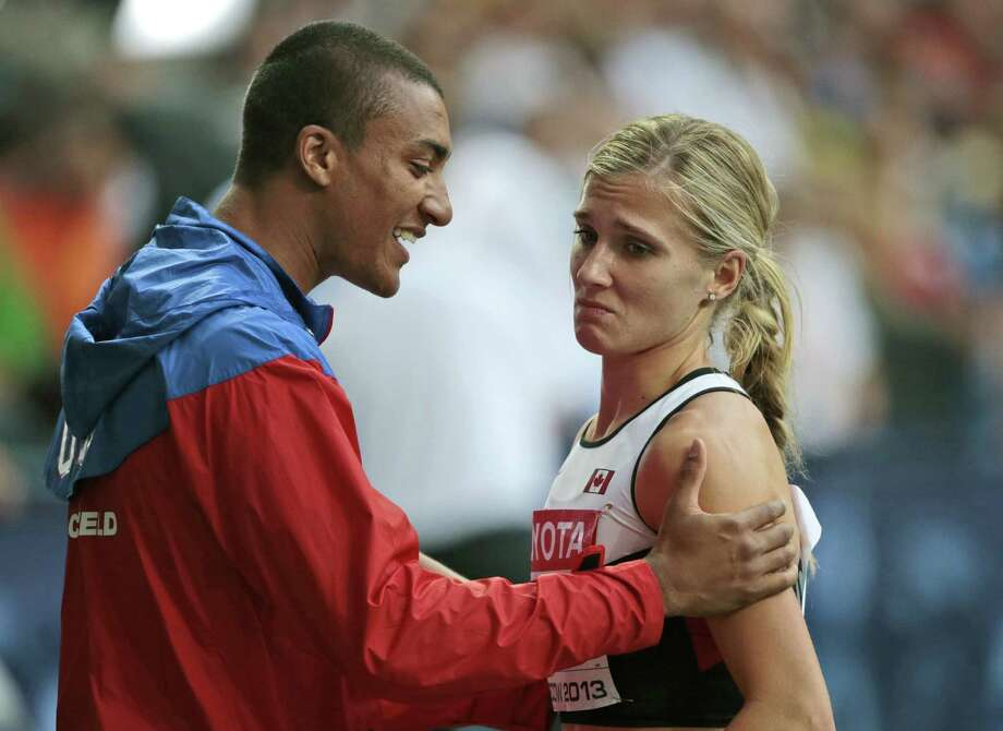 American Ashton Eaton (left) talks with wife Brianne Theisen Eaton of Canada after she won silver in the heptathlon. Photo: Ivan Sekretarev / Associated Press