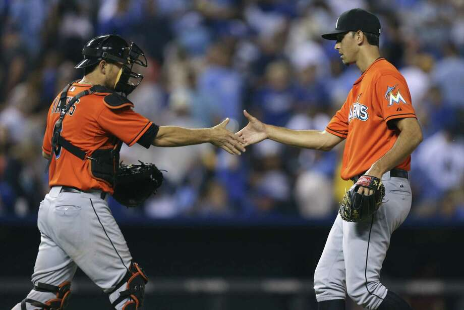 Miami pitcher Steve Cishek celebrates his 25th save of the season with catcher Jeff Mathis. Photo: Ed Zurga / Getty Images