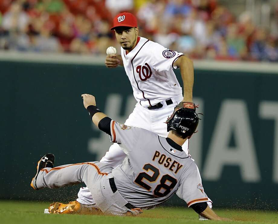 Nationals second baseman Anthony Rendon bobbles the ball but still gets the out as the Giants' Buster Posey slides into second base in the fourth inning. Photo: Alex Brandon, Associated Press