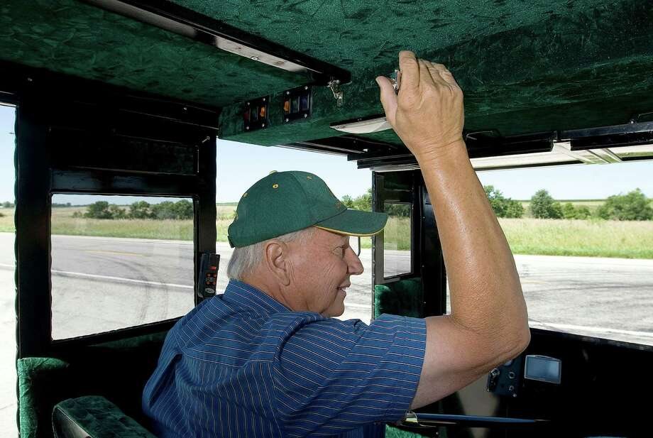 In this July 24, 2013 photo, Larry Yoder turns a lever to operate a turn signal while demonstrating a drive in his solar-powered Amish buggy in Sullivan, Ill. Yoder took a former Amish buggy and built solar panels into the roof to feed batteries that power an electric motor capable of whipping it along at 14 mph, flat out. Photo: Herald & Review, Jim Bowling