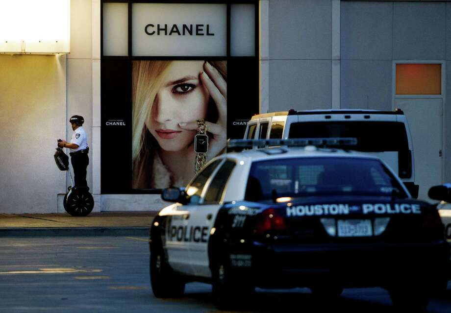 A security guard rides a Segway outside of the Chanel store in the Galleria, Wednesday, Aug. 14, 2013, in Houston. Five suspects burglarized the store fleeing on foot with several purses after their getaway driver left them at the site. Police have two in custody while they continue to seek the remaining four. Photo: Cody Duty, Houston Chronicle / © 2013 Houston Chronicle