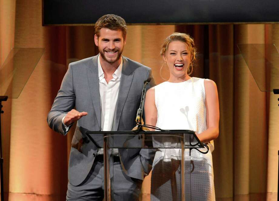 Liam Hemsworth, left, and Amber Heard speak on stage at the Hollywood Foreign Press Association Luncheon at the Beverly Hilton Hotel on Tuesday, Aug. 13, 2013, in Beverly Hills, Calif. (Photo by Chris Pizzello/Invision/AP) ORG XMIT: CAPM141 Photo: Chris Pizzello, AP / Invision