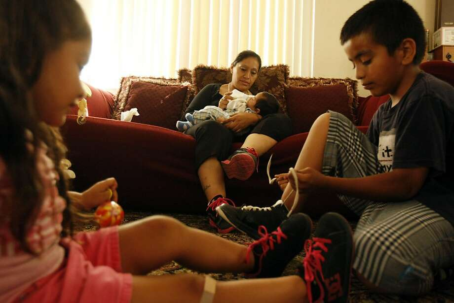 Maria Pulido feeds her youngest son, Joseph, while son Angel shows daughter Nephertytie how to tie her shoelaces. After struggling to lose weight after her pregnancies, Pulido turned to diet pills, which she'll keep using as long as they work. Photo: Rohan Smith, The Chronicle