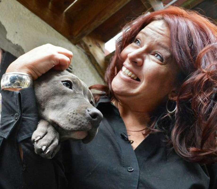 Susan Kittle of Poestenkill with her family's new dog Pearl, one of the pit bull puppies found injured by train tracks, at the Mohawk Hudson Humane Society in Menands Wednesday Dec. 5, 2012. (John Carl D'Annibale / Times Union)