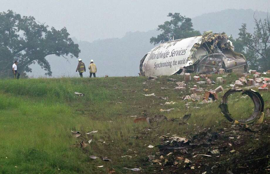 Fire crews investigate where a UPS cargo plane lies on a hill at Birmingham-Shuttlesworth International Airport after crashing on approach, Wednesday, Aug. 14,  2013, in Birmingham, Ala. Toni Herrera-Bast, a spokeswoman for Birmingham's airport authority, says there are no homes in the immediate area of the crash. Photo: Butch Dill