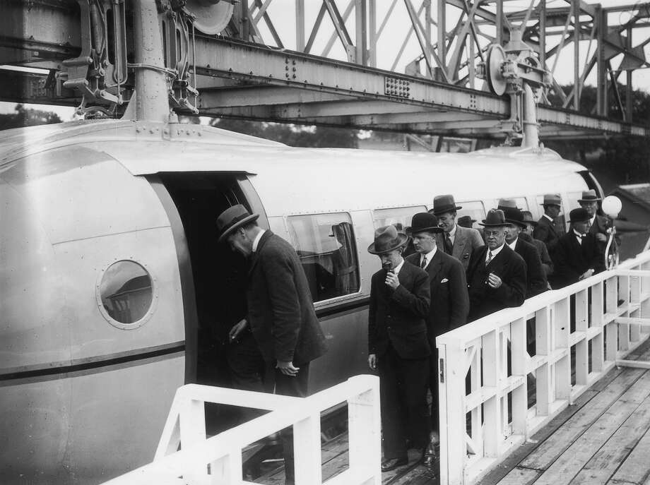 1930:  The first load of passengers queuing for the Bennie Railplane in Glasgow; the inventor George Bennie is third in the queue. The streamlined cars are self propelled, driven by air screws in front and behind, and hang from a steel girder. Photo: J. A. Hampton, Getty Images / Hulton Archive