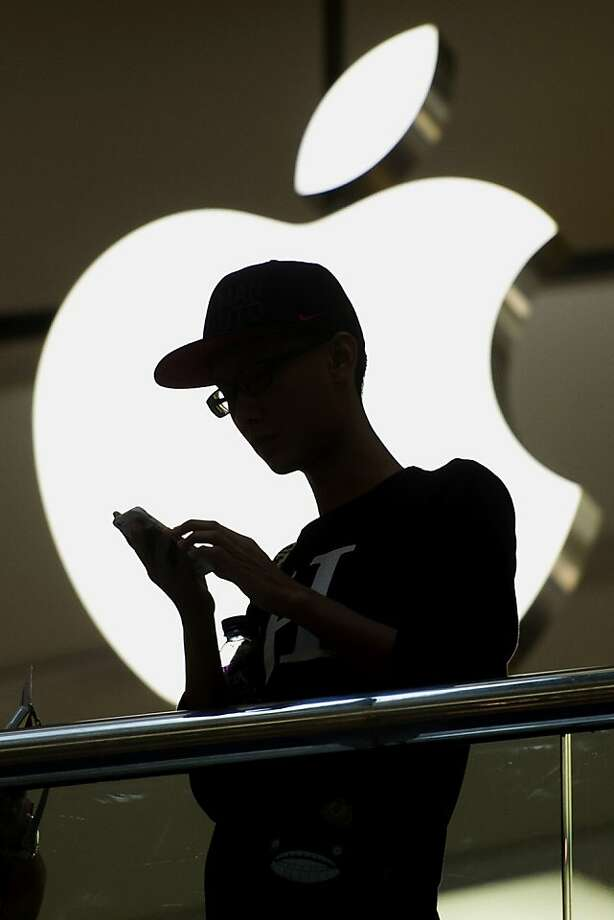 A man looks at his Apple Inc. iPhone in front of the company's store in Hong Kong, China, on Tuesday, July 16, 2013, on Tuesday, July 16, 2013. Apple Inc. is expected to release earnings figures on July 23. Photographer: David Paul Morris/Bloomberg Photo: David Paul Morris, Bloomberg