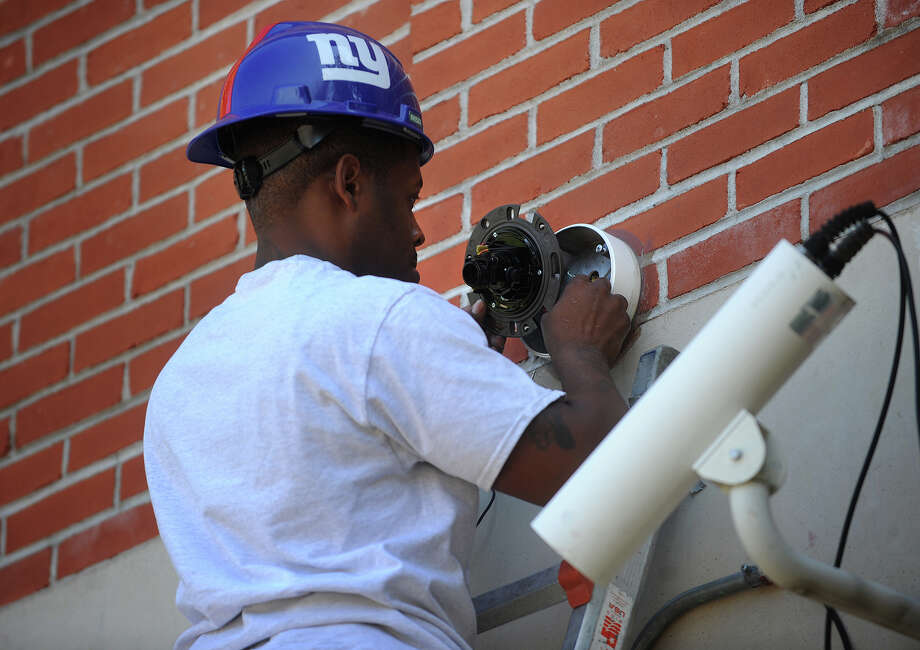Sonitrol employee Ramon Glover, of Bridgeport, installs a new security camera above the front door of Classical Studies Academy at 240 Linwood Avenue in Bridgeport, Conn. on Wednesday, August 14, 2013. Photo: Brian A. Pounds / Connecticut Post