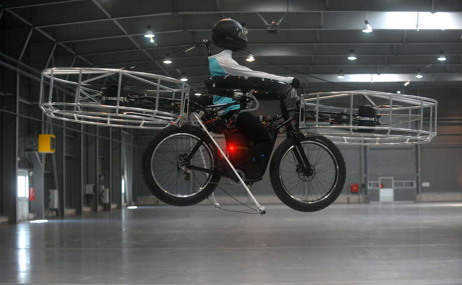 A picture taken on June 12 , 2013 at the hall of Letnany fairground in Prague shows a dummy sitting on the flying bike, a unique construction of Czech designers and modern technology of French company ''Dassault Systemes - 3D software tools''. This bike flies thanks to six futuristic horizontal propellers and an electric motor. (Photo: MICHAL CIZEK/AFP/Getty Images) Photo: Multiple