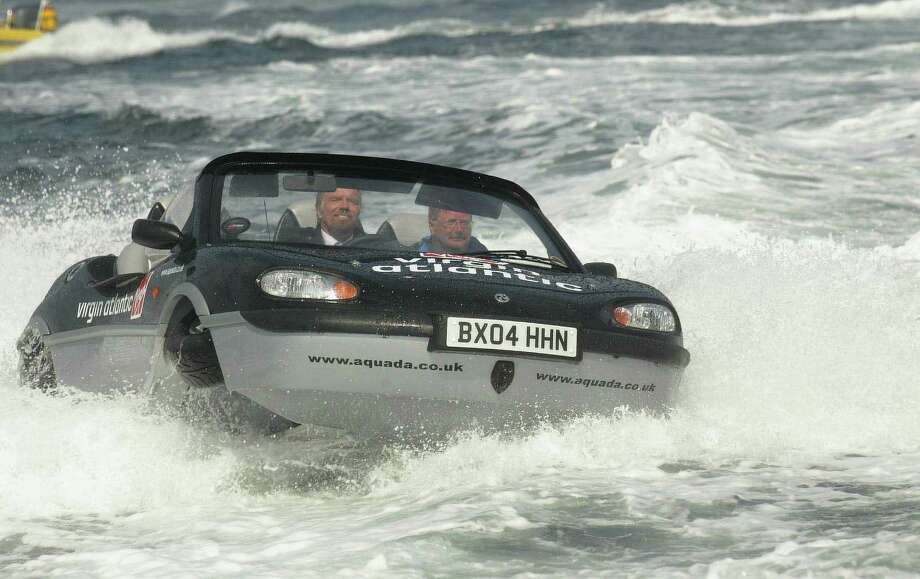 Virgin entrepreneur Richard Branson pilots his Gibbs Aquada amphibious car during a record-breaking crossing of the English Channel June 14, 2004 between Dover, England and Calais, France. Branson broke a French-held record for crossing English Channel aboard an amphibious vessel.  (Photo by Carl De Souza/Getty Images) Photo: Carl De Souza, Multiple / 2004 Getty Images