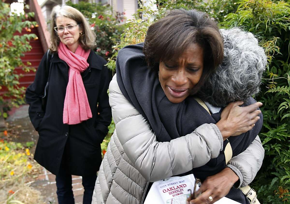Tanya Coke-Kendall (center) hugs Lissa Gardner, a co-worker of Tanya's sister, before concerned friends and family members organize a search for Sandra Coke in Oakland, Calif. on Wednesday, Aug. 7, 2013. At left is Sandra Coke's childhood friend Wendy Springer. Coke, a criminal investigator, has not been seen or heard from since Sunday.