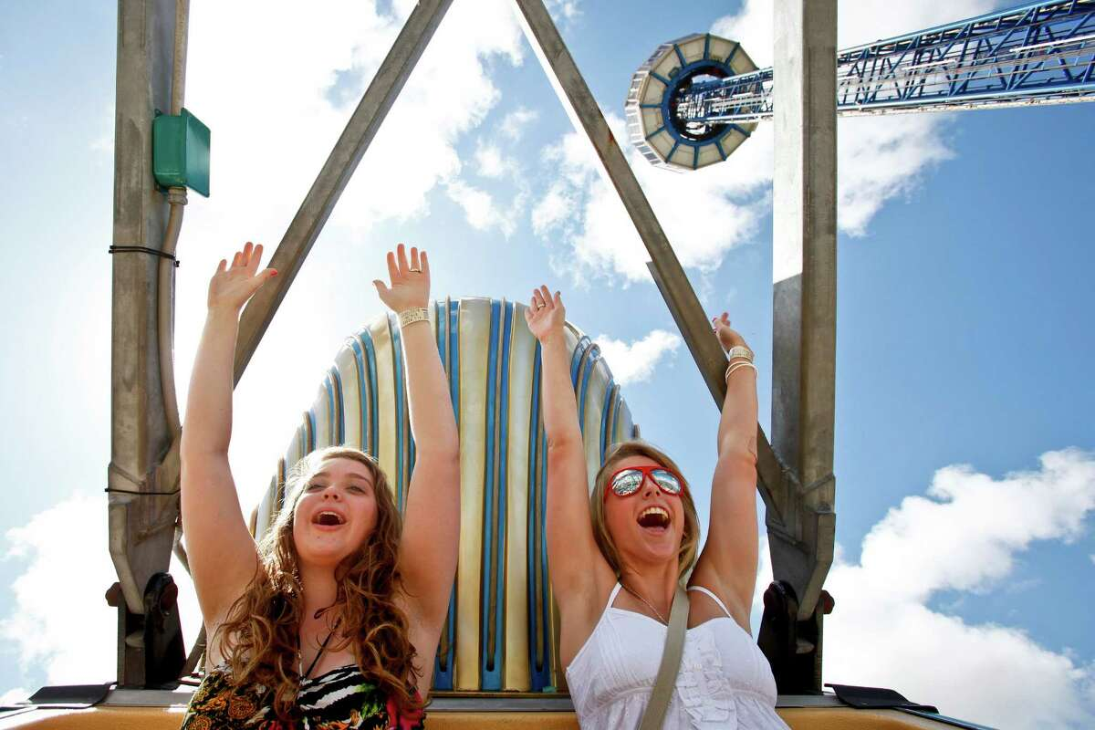 Madison Dickerson, 15, (left) and Laurenn Reynolds (16) throw their arms in the air as they are inverted while riding the