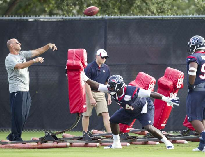 Defensive line coach Bill Kollar, left, throws a football as his unit hits a blocking sled.