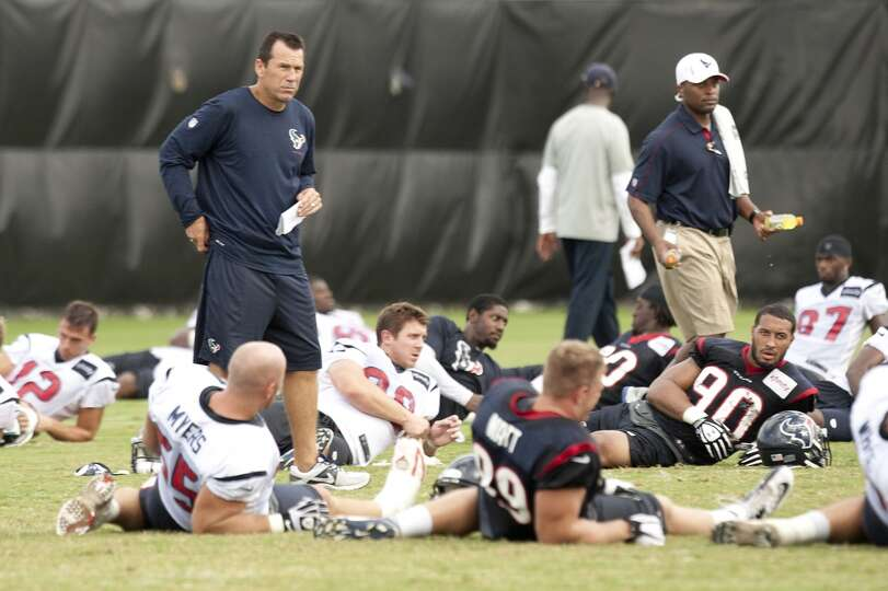 Head coach Gary Kubiak stands amongst his players as they stretch at the end of practice.