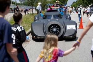 Alexandre Keyes gets a look at John Salazar's Batcar, as about 300 artful vehicles of all shapes and sizes lined up down Allen Parkway before the 26th annual Houston Art Car Parade May 11, 2013, in Houston.