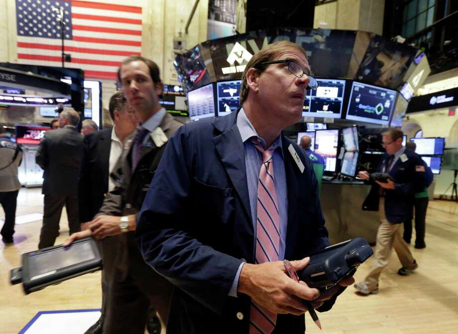 In this Tuesday, Aug. 13, 2013, photo, traders work on the floor of the New York Stock Exchange.  Good news from two of Europe's biggest economies failed to shake global stock markets out of their lethargy Wednesday Aug. 14, 2013. (AP Photo/Richard Drew) ORG XMIT: NYBZ130 Photo: Richard Drew / AP