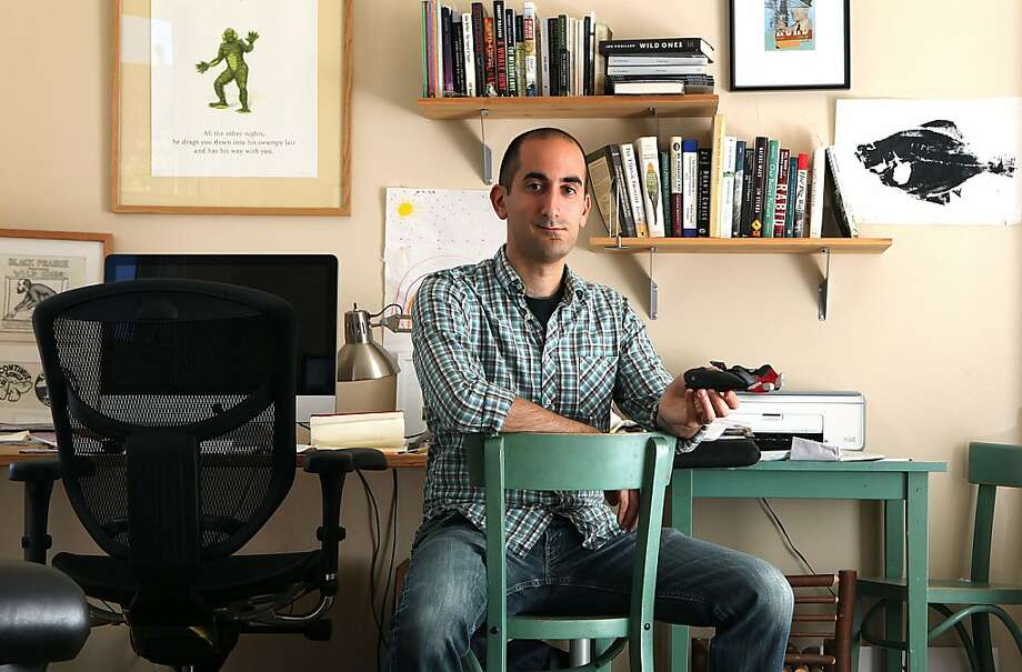 "Jon Mooallem, author of ""Wild Ones,"" has lots of objects shaped like animals. Here, at his office at home in San Francisco, he shows a pewter whale bottle opener - the whale is wearing lipstick. His bottom-line message: that the world's wild animals ought to be saved from extinction. Photo: Liz Hafalia, The Chronicle"