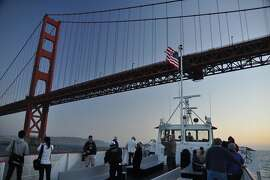 A Red and White Fleet boat goes under the Golden Gate Bridge.