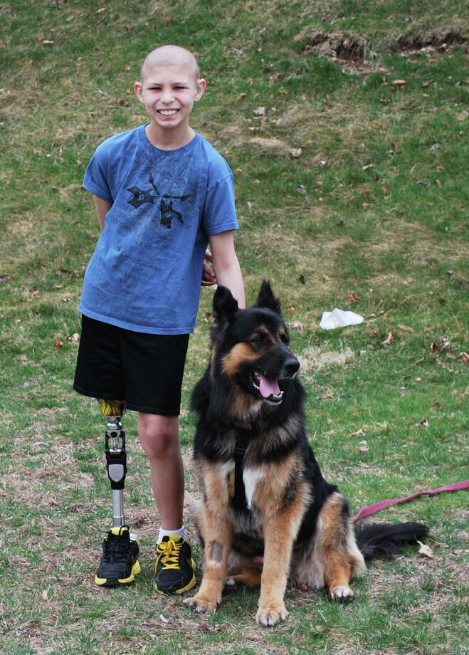 Marik Tucker, a cancer patient who had his right leg amputated in 2012, is shown with his dog, Zero. The German Shepherd died this week, just months after he was adopted by the Tucker family from the Oxford Animal Shelter. Photo: Contributed Photo / Connecticut Post Contributed