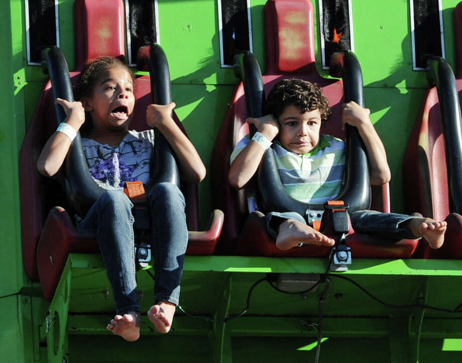 At left, Amaya Jones, 9, and her brother, Jaden, 5, of Norwalk, react to a steep drop on an amusement ride during the annual Carnival of Fun at St. Catherine of Siena Church in Riverside, Wednesday night, August 14, 2013, celebrating the 100th Anniversary of the Parish. Photo: Bob Luckey / Greenwich Time