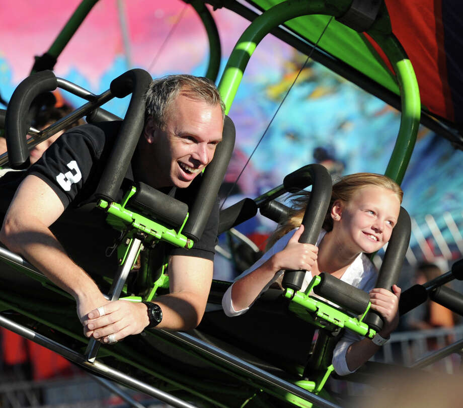 At left, Lars Norell of Old Greenwich, rides the Rip Chord with his daughter, Ellen, 8, during the annual Carnival of Fun at St. Catherine of Siena Church in Riverside, Wednesday night, August 14, 2013, celebrating the 100th Anniversary of the Parish. Photo: Bob Luckey / Greenwich Time