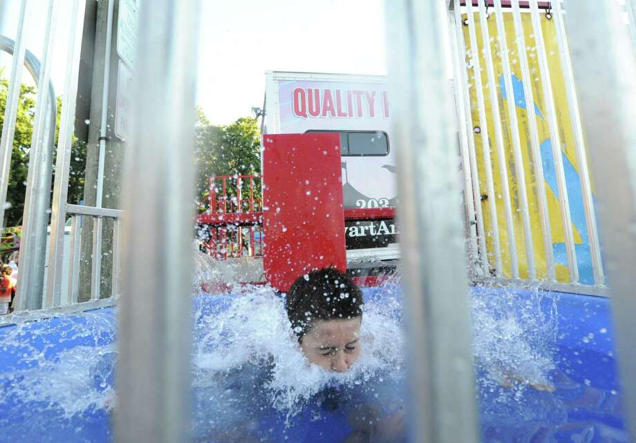 Kai Lammers, 12, of Greenwich, falls into the water of a dunk-tank that was triggered by a softball throw from the arm of Duff Haffenreffer (not in photo), 11, of Riverside, during the annual Carnival of Fun at St. Catherine of Siena Church in Riverside, Wednesday night, August 14, 2013, celebrating the 100th Anniversary of the Parish. Photo: Bob Luckey / Greenwich Time
