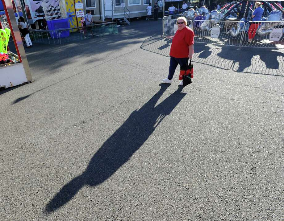 Janis Pataky of Greenwich casts a long shadow while walking the grounds during the annual Carnival of Fun at St. Catherine of Siena Church in Riverside, Wednesday night, August 14, 2013, celebrating the 100th Anniversary of the Parish. Pataky is the Director of Faith Formation at the church. Photo: Bob Luckey / Greenwich Time