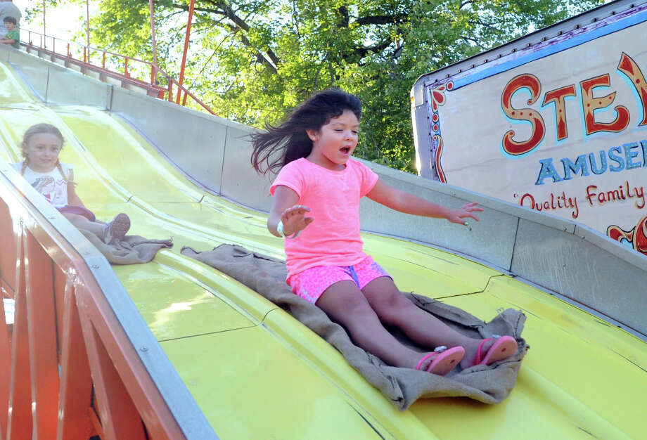 At right, Olivia Audrighetti, 6, of Greenwich, screams as she descends on the Big Slide during the annual Carnival of Fun at St. Catherine of Siena Church in Riverside, Wednesday night, August 14, 2013, celebrating the 100th Anniversary of the Parish. Photo: Bob Luckey / Greenwich Time