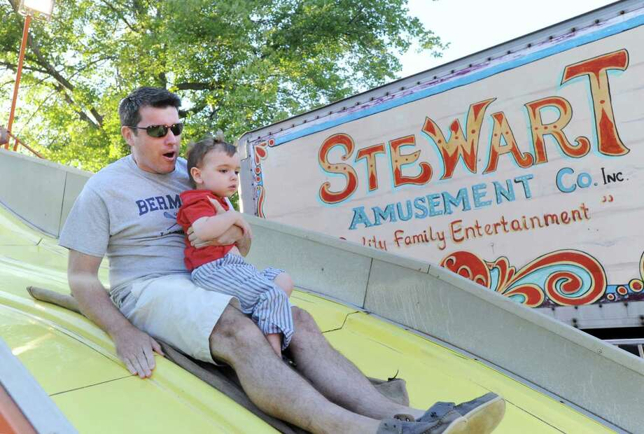 Mike O'Donnell of Old Greenwich holds onto his son, Michael, 2, as the duo enjoyed the Big Slide ride at the annual Carnival of Fun at St. Catherine of Siena Church in Riverside, Wednesday night, August 14, 2013, celebrating the 100th Anniversary of the Parish. Photo: Bob Luckey / Greenwich Time