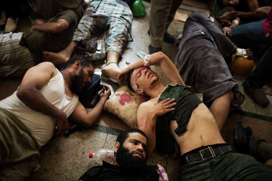 Wounded supporters of ousted Islamist President Mohammed Morsi lie on the floor of a makeshift hospital at a sit-in at Cairo's Nasr City district, Egypt, Wednesday, Aug. 14, 2013. Egyptian police in riot gear swept in with armored vehicles and bulldozers Wednesday to clear two sprawling encampments of supporters of the country's ousted Islamist president in Cairo, showering protesters with tear gas as the sound of gunfire rang out. Photo: Manu Brabo, Associated Press / AP