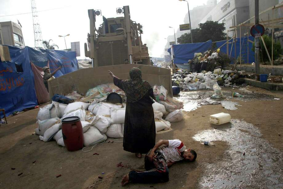 \An Egyptian woman tries to stop a military bulldozer from hurting a wounded youth during clashes that broke out as Egyptian security forces moved in to disperse supporters of Egypt's deposed president Mohamed Morsi in a huge protest camp near Rabaa al-Adawiya mosque in eastern Cairo on August 14, 2013. The operation began shortly after dawn when security forces surrounded the sprawling Rabaa al-Adawiya camp in east Cairo and a similar one at Al-Nahda square, in the centre of the capital, launching a long-threatened crackdown that left dozens dead. Photo: MOHAMMED ABDEL MONEIM, AFP/Getty Images / AFP