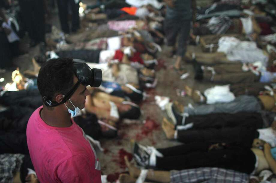 A man looks at bodies laid out in a make shift morgue after Egyptian security forces stormed two huge protest camps at the Rabaa al-Adawiya and Al-Nahda squares where supporters of ousted president Mohamed Morsi were camped,  in Cairo, on August 14, 2013. Egypt's bloody crackdown on supporters of  Morsi triggered widespread condemnation as the international community reacted with alarm to the deepening crisis. The action has resulted in more than 120 deaths, according to AFP reporters at the scene. Photo: MOSAAB EL-SHAMY, AFP/Getty Images / AFP