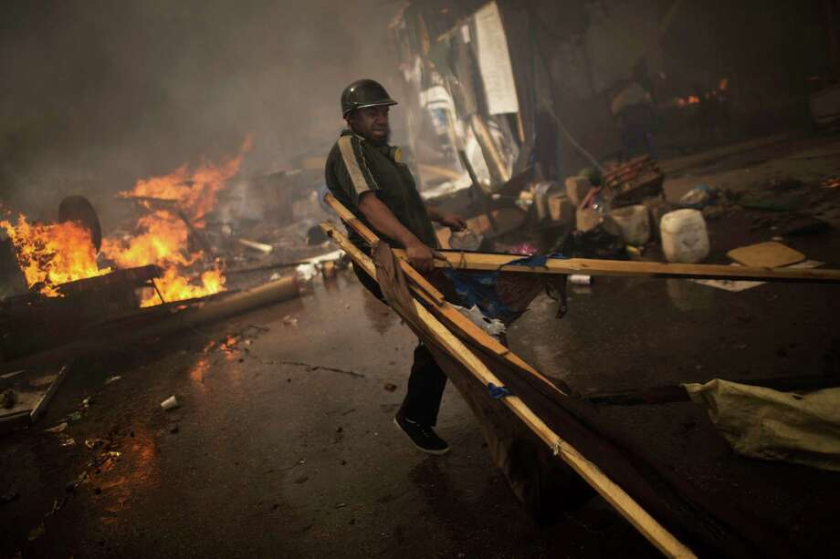 A supporter of ousted Egyptian President Mohammed Morsi carries wood to burn in a fire barricade at the sit-in at Rabaa Al-Adawiya Square in Cairo's Nasr City district, Egypt, Wednesday, Aug. 14, 2013. Egyptian police in riot gear swept in with armored vehicles and bulldozers Wednesday to clear two sprawling encampments of supporters of the country's ousted Islamist president in Cairo, showering protesters with tear gas as the sound of gunfire rang out. Photo: Manu Brabo, Associated Press / AP