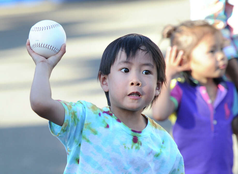 Ethan De Los Reyes, 5, of Stamford, throws a softball at the dunk-tank trigger during the annual Carnival of Fun at St. Catherine of Siena Church in Riverside, Wednesday night, August 14, 2013, celebrating the 100th Anniversary of the Parish. Photo: Bob Luckey / Greenwich Time
