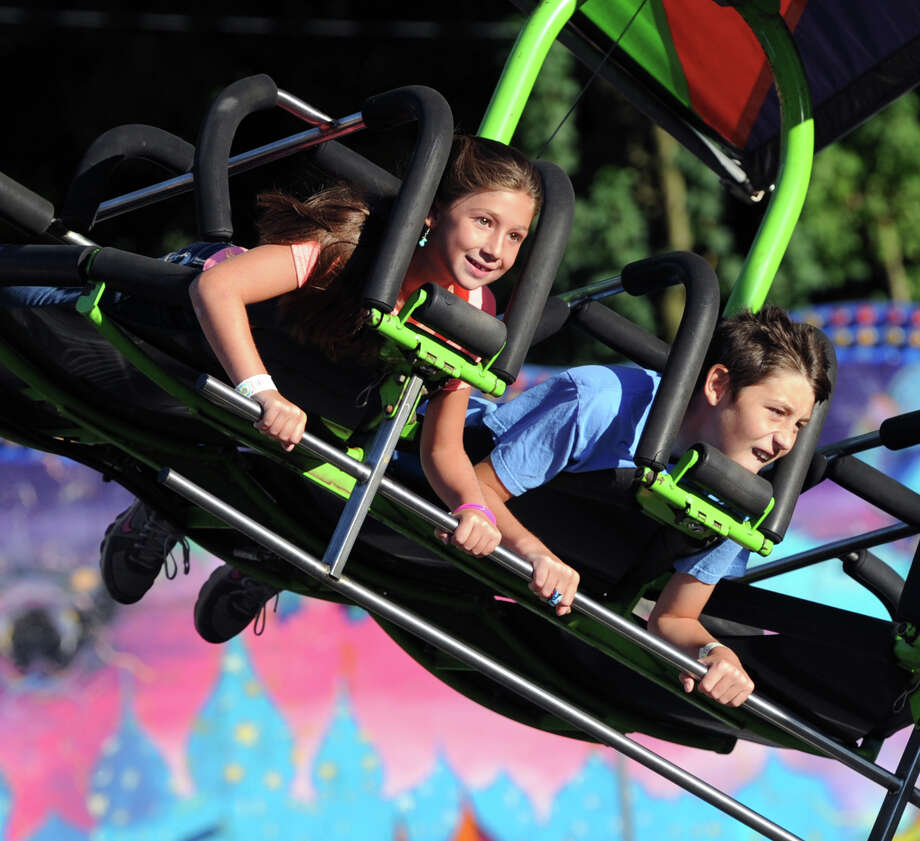 Greenwich residents, Reagan Waurishuk, 9, and her brother, Tommy (at right), 13, on an amusement ride during the annual Carnival of Fun at St. Catherine of Siena Church in Riverside, Wednesday night, August 14, 2013, celebrating the 100th Anniversary of the Parish. Photo: Bob Luckey / Greenwich Time