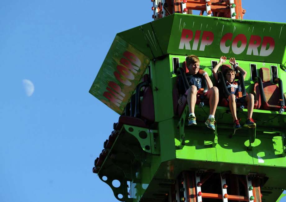 At left, Brendan Wise, 13, of Greenwich, and friend, J.J. von Oiste, also, 13, of Rye, N.Y., take a plunge on an amusement ride during the annual Carnival of Fun at St. Catherine of Siena Church in Riverside, Wednesday night, August 14, 2013, celebrating the 100th Anniversary of the Parish. Photo: Bob Luckey / Greenwich Time
