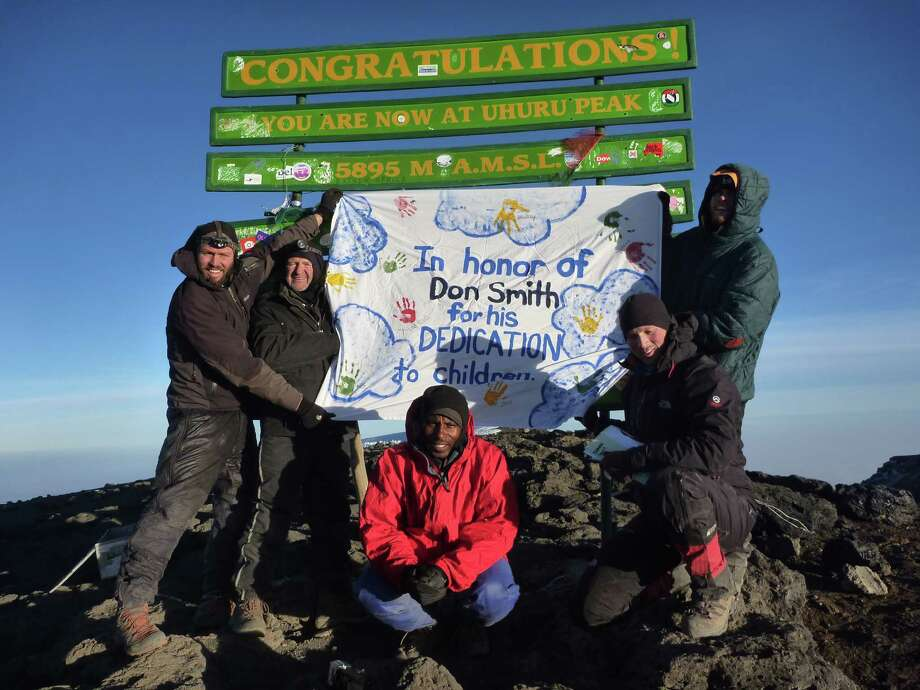 Ed Kampf (second from left) holds a banner honoring lifelong friend Don Smith at the peak of Mount Kilimanjaro in Africa. Kampf, of Albany, climbed Kilimanjaro in July and raised more than $6,000 for St. Catherine's Center for Children. Smith worked at the center for nearly 40 years.