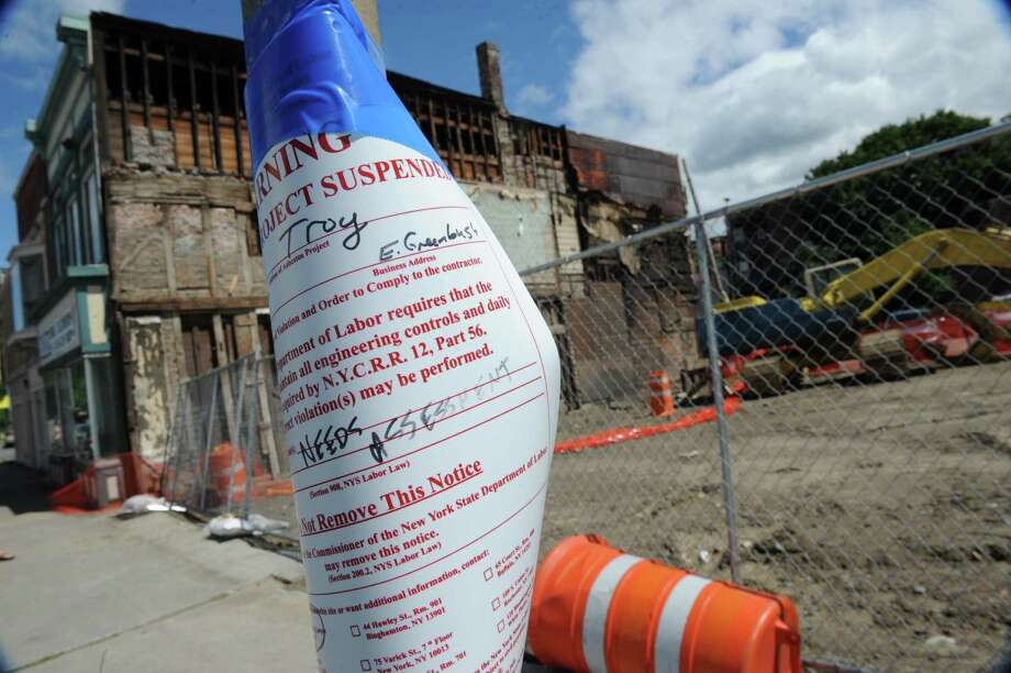 A cease and desist notice at the demolition site  Wednesday, Aug. 14, 2013, on King St. in Troy, N.Y., where buildings 4, 6, 8 and 10 were torn down. The state labor department issued a stop-work order at the site over asbestos concerns. (Lori Van Buren / Times Union) Photo: Lori Van Buren / 00023518A