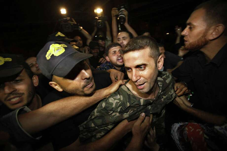 A freed Palestinian prisoner laughs as relatives and friends gather upon his arrival to his family house in Gaza City. Photo: Adel Hana / Associated Press