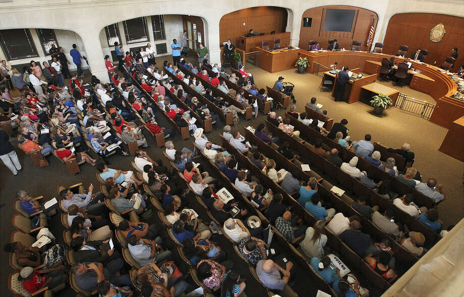ABOVE: People pack the City Council chambers to voice their opinions regarding the proposed anti-discrimination policy change. LEFT:  Residents opposed to the policy change gather on the steps of City Hall for a prayer vigil prior to appearing before the council. Photo: Photos By Kin Man Hui / San Antonio Express-News