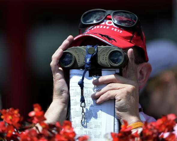 A racing patron is deep in concentration while watching the racing Wednesday afternoon, Aug. 14, 2013, at the Saratoga Race Course in Saratoga Springs, N.Y.   (Skip Dickstein/Times Union) Photo: SKIP DICKSTEIN