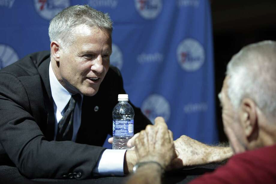 New Philadelphia 76ers coach Brett Brown, a former Spurs assistant, greets an audience member during Wednesday's news conference making his hiring official. Photo: Matt Rourke / Associated Press