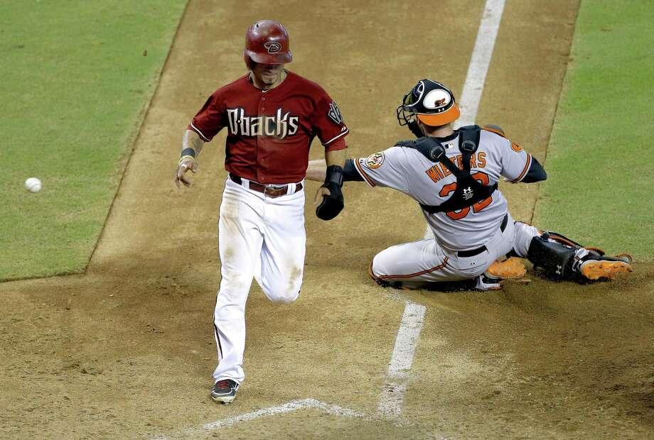 Baltimore catcher Matt Wieters can't corral the ball as Arizona's Gerardo Parra scores the winning run. Photo: Matt York / Associated Press