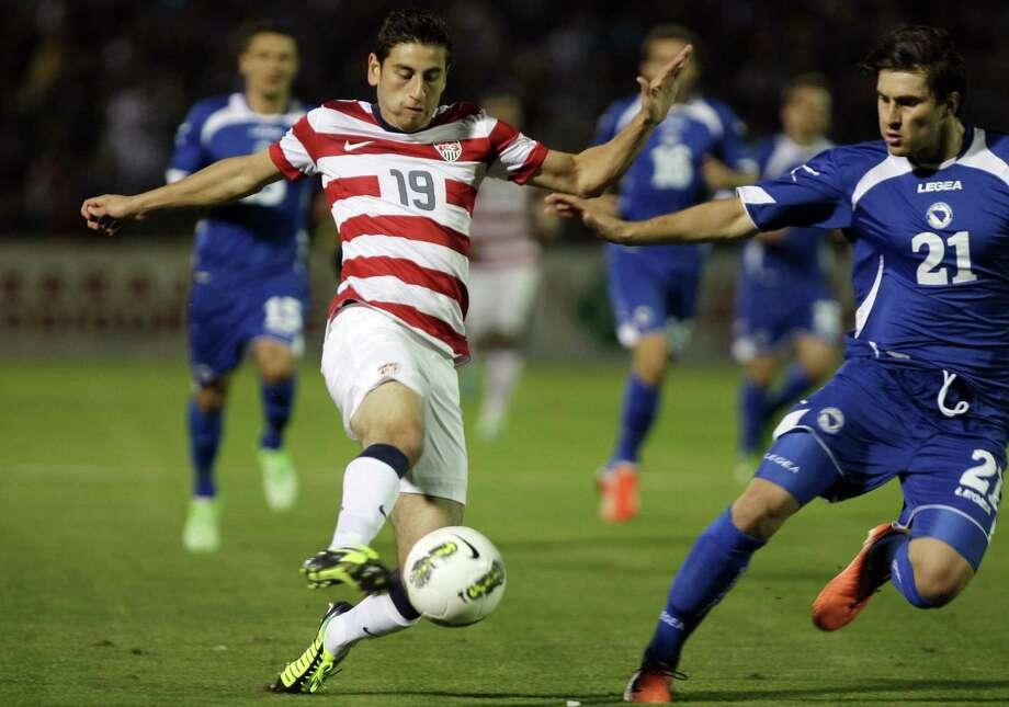 American Alejandro Bedoya (left) reaches for the ball against Bosnia-Herzegovina's Ervin Zukanovic. Photo: Amel Emric / Associated Press