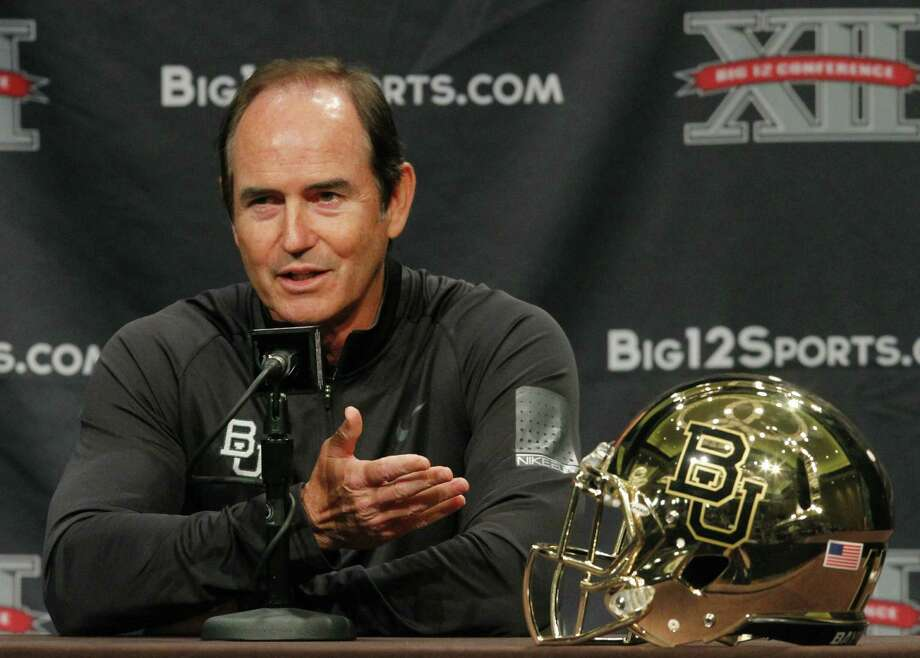"""Coach Art Briles showed off Baylor's new gold helmet at Big 12 media days last month. This kind of """"branding"""" — along with recent success on the field — has helped the Bears transform into a cutting-edge program. Photo: Tim Sharp / Associated Press"""
