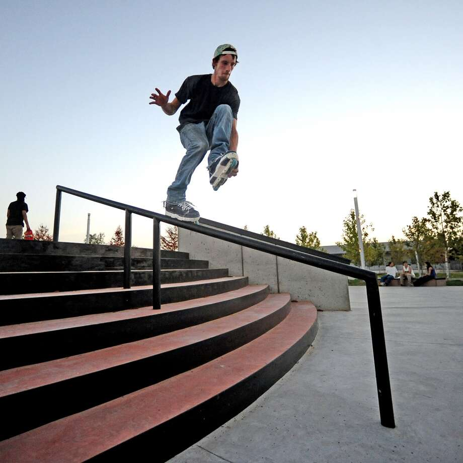 Local comedian Jack Neil lands a grabbed makio down the handrail at the Beautiful Mountain Skate Plaza on Tuesday, August 6, 2013. Photo taken: Randy Edwards/The Enterprise Photo: Beaumont Enterprise